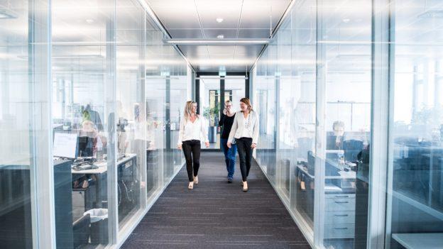 Mitarbeiterinnen laufen Gang entlang